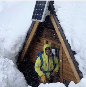 California Mountain Guide JB Brown standing outside of the Peter Grubb Hutt on a big snow year